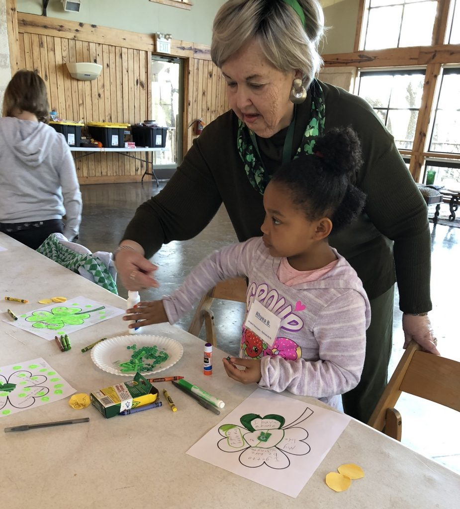 Ann helps a child complete a special St. Patrick's Day activity as part of our Youth Program at Retreat 170 in Texas earlier this year.